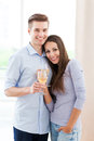 Couple having toast in new home drinking wine modern apartment Stock Photography