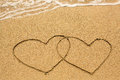 Couple of hearts drawn on the beach sand in sunny day. Love. Royalty Free Stock Photo