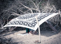 Couple hidden at the beach a under an tent made with tribal blanked stretched to wood pole and dead trees Stock Photo