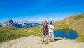 Couple of hiker on the mountain top looking at blue lake and mountain peaks. Summer adventures on the Alps. Wide angle view from a Royalty Free Stock Photo