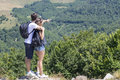 Couple of hikers with backpacks standing at viewpoint and enjoyi enjoying a valley view s shared activity Stock Image