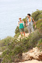 Couple of hikers visiting natural landscape by the sea on a hiking day Royalty Free Stock Photography