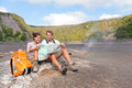 Couple hiking on volcano on hawaii looking at map happy young men and women relaxing taking break in beautiful volcanic landscape Stock Photo