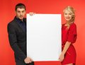 Couple holding big blank board bright picture of Royalty Free Stock Images