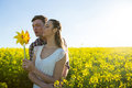 Couple holding blowing pinwheel in mustard field Royalty Free Stock Photo