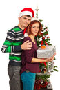 Couple holding christmas present in front of tree Royalty Free Stock Images