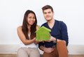 Couple Holding Green House Model At New Home Royalty Free Stock Photo