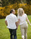 Couple holding hands with back to camera running through park Royalty Free Stock Photos