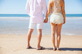 Couple holding hands at the beach rear view of a young standing in front of and during their honeymoon Royalty Free Stock Photography