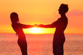 Couple holding hands at beach during sunset silhouette loving partners are spending quality time together side view of men and Royalty Free Stock Photography