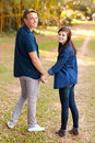 Couple holding hands cute teenage and looking back Royalty Free Stock Photo
