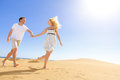 Couple holding hands running having fun under sun in playful and romantic relationship and blue sky in desert two young Stock Images