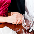 Couple holding hands on a table Stock Images