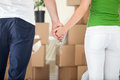Couple holding hands together in new home lot of cardboard boxes background Royalty Free Stock Images
