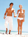 Couple holding hands and walking on the beach Stock Photos
