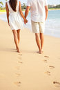 Couple holding hands walking on beach on vacation romantic travel holidays leaving footprints in the sand closeup of feet and Royalty Free Stock Photos