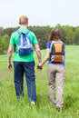 Couple holding hands and walking on a grass field back view of Stock Photography