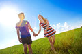 Couple holding hands and walking in green field Royalty Free Stock Photo