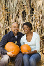 Couple holding pumpkins. Stock Photo