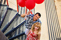 Couple holding red balloons young happy with on the bridge Royalty Free Stock Photos