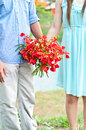 Couple holding red flowers are standing and Stock Photography