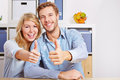 Couple holding thumbs up in living Stock Images