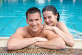Couple in holidays posing at hotel pool edge happy enjoying their the Royalty Free Stock Photography