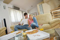 Couple at home eating pizza happy young eat fresh relaxing and watch tv Royalty Free Stock Photo