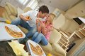 Couple at home eating pizza happy young eat fresh relaxing and watch tv Stock Images