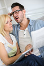 Couple at home reading bad news with horrified look Royalty Free Stock Photography