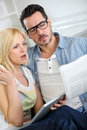 Couple at home reading news with surprised look horrified Royalty Free Stock Images