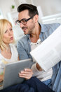 Couple at home reading surprising news on both internet and paper Royalty Free Stock Images