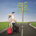 Couple honeymoon travel with luggages and road sign Royalty Free Stock Photos