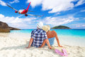 Couple in hug on the beach watching flying aircraft Stock Photos