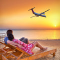 Couple in hug watching airplane at sunset flying into the Stock Photo