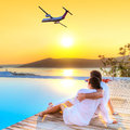 Couple in hug watching airplane at sunset flying into the Stock Photography