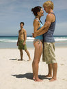 Couple hugging another man in the background on beach men looking on Royalty Free Stock Photo