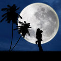 Couple hugging under full moon at beach silhouette of a young passionately blue Stock Photos