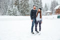 Couple in ice skates hugging and looking at camera outdoors Royalty Free Stock Photo
