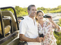 Couple by jeep with binoculars smiling adult standing Royalty Free Stock Image