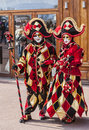 Couple of jesters annecy france february portrait an unidentified disguised in red costumes pose in front a traditional store Stock Photo
