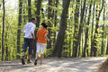 Couple jogging in forest, view from behind. Royalty Free Stock Images