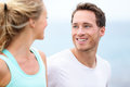 Couple jogging training together running on beach living healthy lifestyle man runner smiling at women during workout closeup of Stock Images