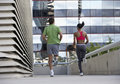 Couple jogging on urban elevated walkway running side by side rear view surface level Stock Photos