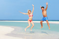 Couple jumping on beautiful tropical beach having fun Stock Photography