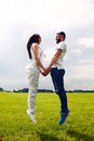Couple jumping on the green field happy holding hands and Royalty Free Stock Photo