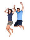 Couple jumping high in the air for joy young men and women leaping with their arms raised isolated on white Royalty Free Stock Image