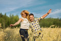 Couple jumping in rye field happy on sunny summer day Stock Photography
