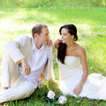Couple just married sitting in park grass Stock Photo