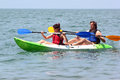 Couple of kayakers rowing in sea water Royalty Free Stock Photo